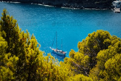 White yacht take a shelter in beautiful blue lagoon of Assos village Kefalonia. Frame between top of
