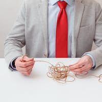 Alone businessman try to unwinds tangled thread ball like puzzle out situation. Conceptual photo.