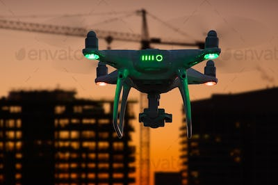 Silhouette of Drone In The Air Over Buildings Under Construction