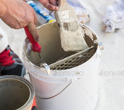 Professional Painter Loading Paint Onto Brush From Bucket