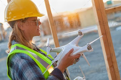 Female Unmanned Aircraft System (UAS) Quadcopter Drone Pilot Holding Drone at Construction Site