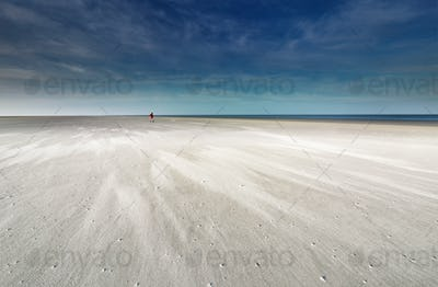 lone man walking on sand beach by North sea