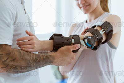 Tattooed physiotherapist who puts an orthosis on the hand of a young patient after an accident