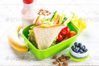 Lunch box with sandwich, vegetables, berries and nuts