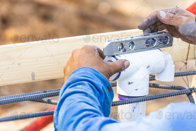 Plumber Using Level While Installing PVC Pipe At Construction Site