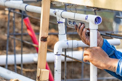 Plumber Using Level While Installing PVC Pipe At Construction Site.