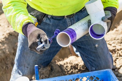 Plumber Applying Pipe Cleaner, Primer and Glue to PVC Pipe At Construction Site