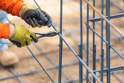 Worker Securing Steel Rebar Framing With Wire Plier Cutter Tool At Construction Site