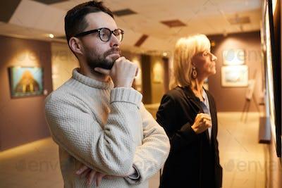 Two People Looking at Paintings in Art Gallery