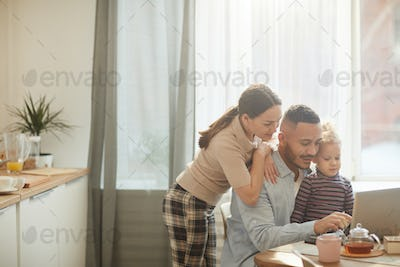 Modern Family Using Laptop in Cozy Kitchen