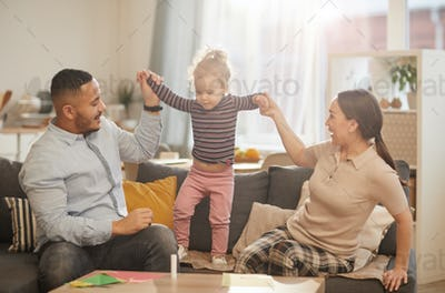 Happy Family Playing with Cute Little Daughter at Home