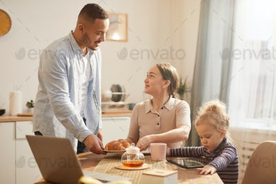 Modern Family Using Gadgets at Breakfast in Cozy Kitchen