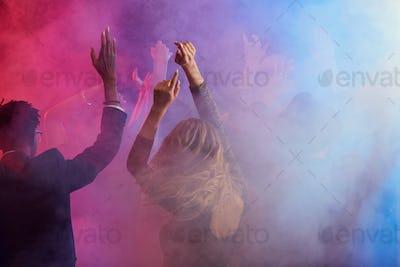 Dancing Crowd in Smoky Nightclub