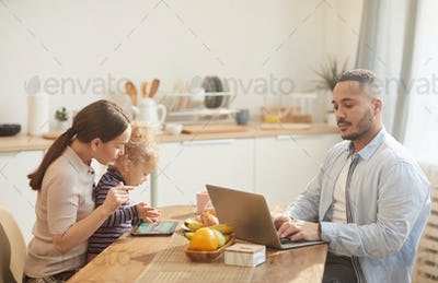 Modern Family Using Gadgets at Breakfast