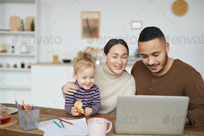 Happy Mixed-Race Family Using Laptop at Home