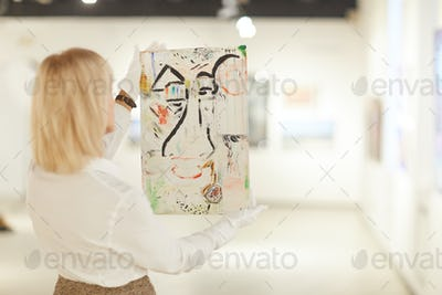 Woman Holding Abstract Painting in Art Gallery