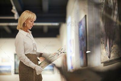 Female Art Expert Holding Painting