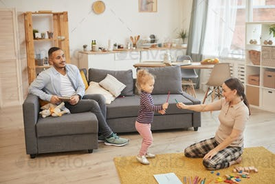 Young Family Playing with Little Kid at Home