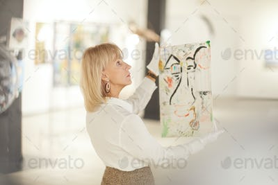 Elegant Woman Holding Painting in Art Gallery