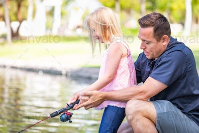Young Caucasian Father and Daughter Having Fun Fishing At The Lake