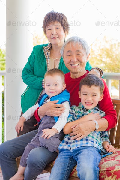 Senior Adult Chinese Couple Sitting With Their Mixed Race Grandchildren