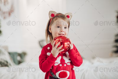 Lovely little girl in red dress with Christmas present