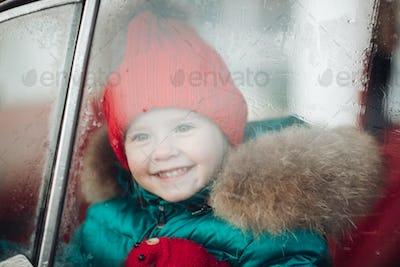 Smiling cute winter girl in red hat sitting in car having fun