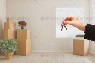 Handing Over House Keys In Room with Packed Moving Boxes