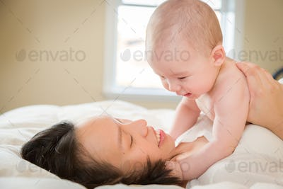 Mixed Race Chinese and Caucasian Baby Boy Laying In Bed with His Mother