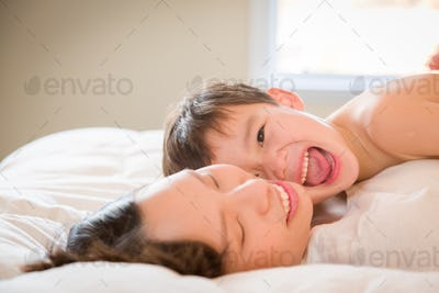 Mixed Race Chinese and Caucasian Boy Laying In His Bed with His Mother.