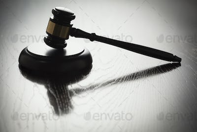Dramatic Gavel Silhouette on Reflective Wood