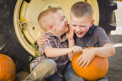 Two Boys Sitting Against Tractor Tire Holding Pumpkins Whispering Secrets