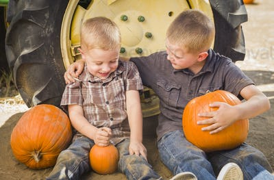 Two Boys Holding Pumpkins Talking and Sitting Against Tractor Tire
