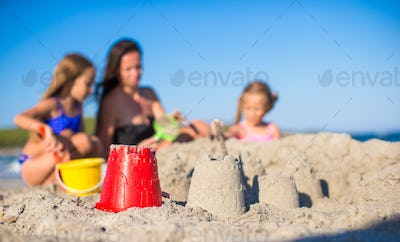 Happy family playing with beach toys during tropical vacation