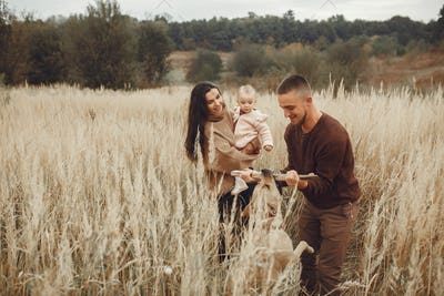 Cute and stylish family playing in a autumn field