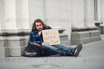 Homeless man in a durty clothes autumn city