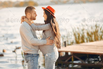 Pregnant wife with her husband standing near river