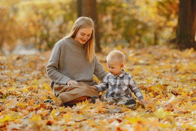 Mother with little son playing in a autumn field