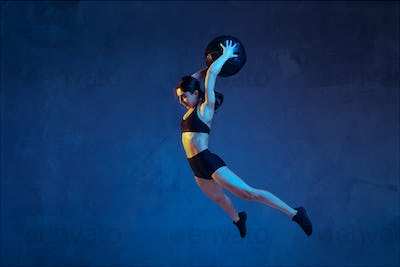 Caucasian young female athlete practicing on blue studio background in neon light