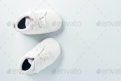 Tiny baby shoes on pastel background