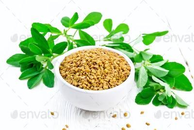 Fenugreek with green leaves in bowl on wooden board