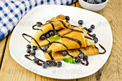 Pancakes with blueberries and chocolate on board