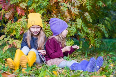 Two adorable girls outdoors in autumn forest