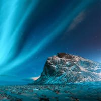 Aurora borealis above the snowy mountains and sandy beach