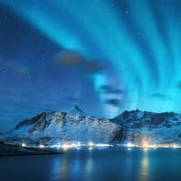 Aurora borealis over the sea, snowy mountains and city lights