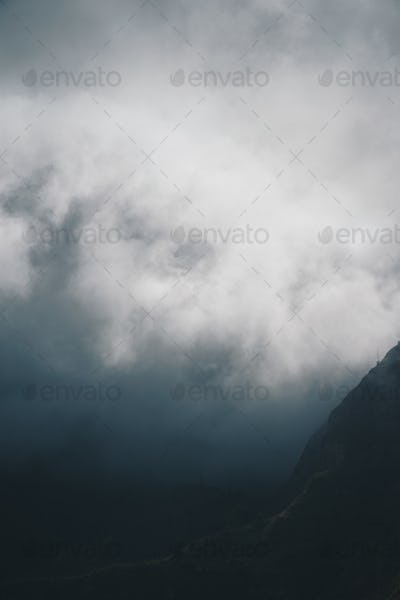 Moody scenery with mist flowing over huge mountain slope and spilling into the green valley. Santo