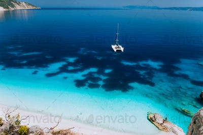 White catamaran yacht drift on clear azure water surface in calm blue lagoon with transparent water