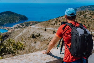 Male summer holiday vacation on Kefalonia Greece. Photographer with backpack enjoying capture of