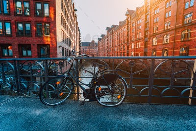Old bicycle parked against iron hand railing on bridge in Hamburg warehouse district