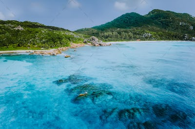 Tropical coastline of La Digue island with granite boulders and paradise beaches, view from the sea